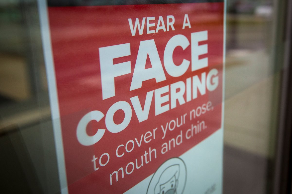 FILE - A sign advising to wear a face covering at a shopping centre in Kingston, Ontario on Thursday, December 10, 2020.