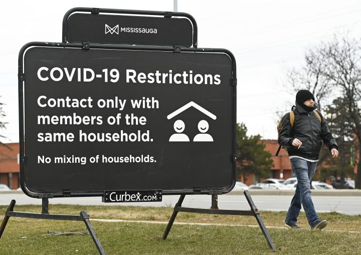 A person walks past a COVID-19 restrictions sign during the COVID-19 pandemic in Mississauga, Ont., on Tuesday, December 22, 2020.