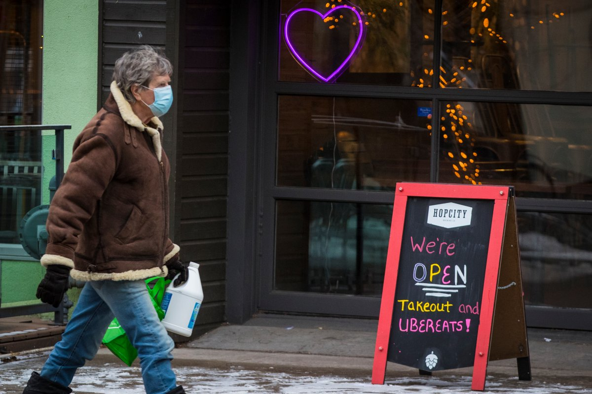 A person wears a disposable mask while walking past a restaurant that offers take-out and ubereats in Kingston, Ontario on Wednesday, December 30, 2020, as the COVID-19 pandemic continues across Canada and around the world.