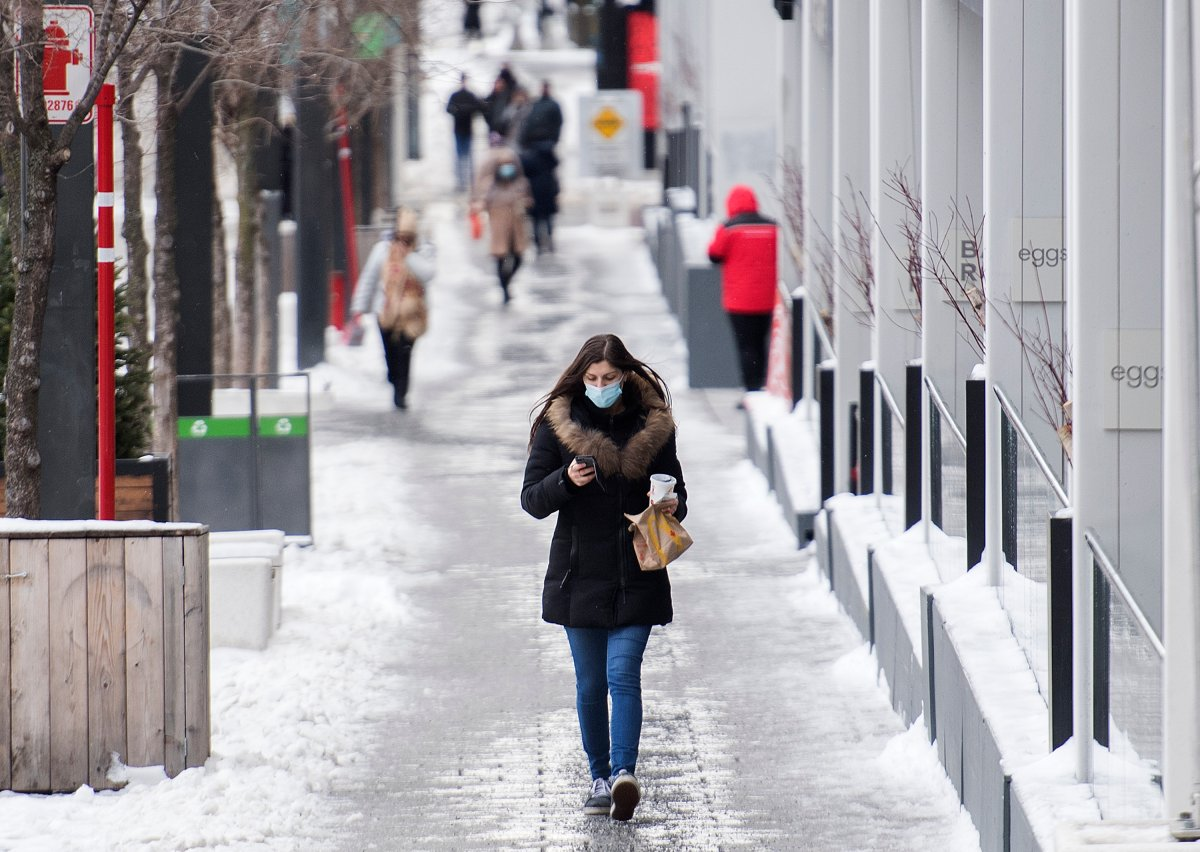 A woman wears a face mask as she walks along a street in Montreal, Thursday, December 31, 2020.