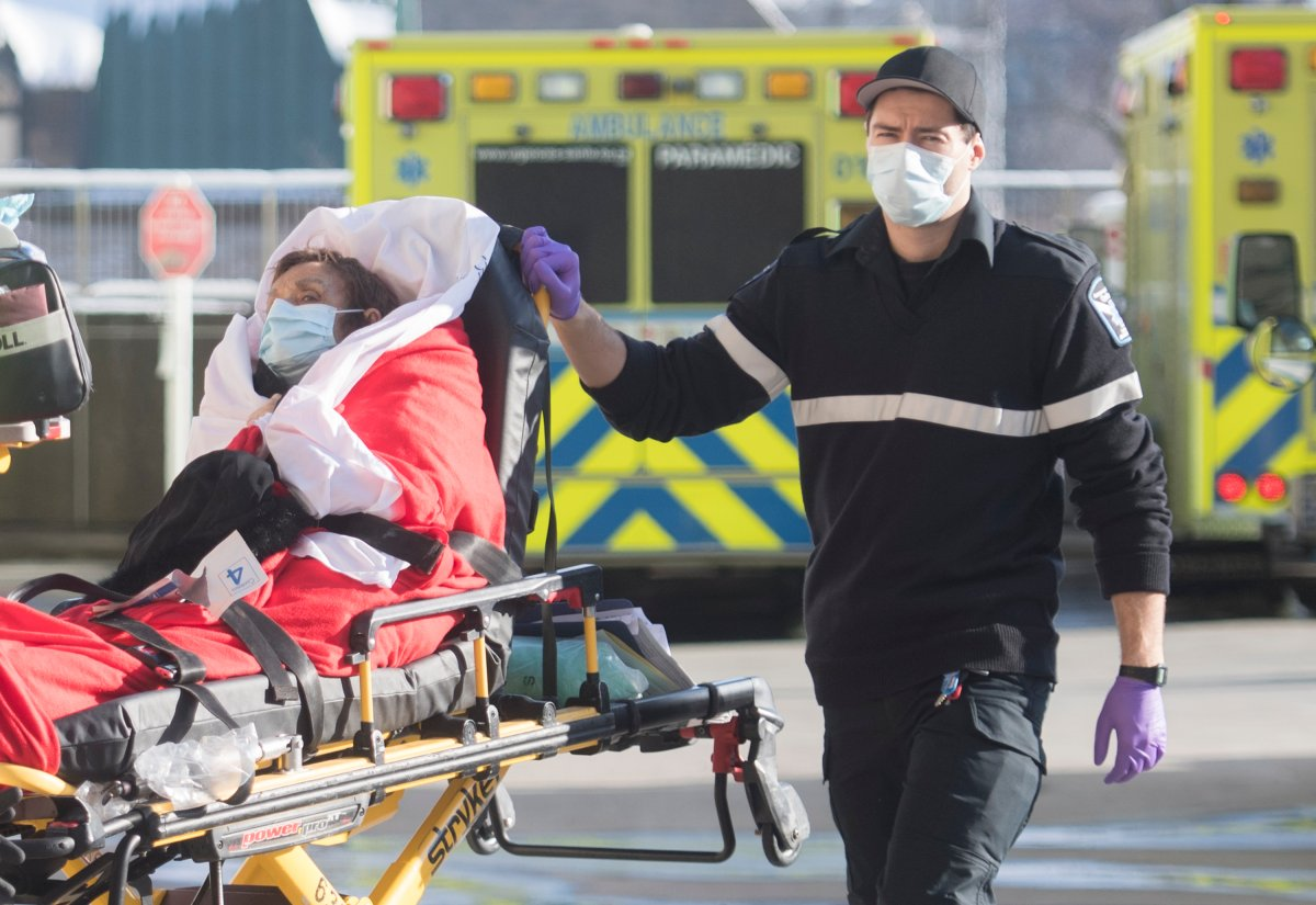 A paramedic transfers a woman from an ambulance into a hospital in Montreal, Saturday, Jan. 2, 2021, as the COVID-19 pandemic continues in Canada and around the world.
