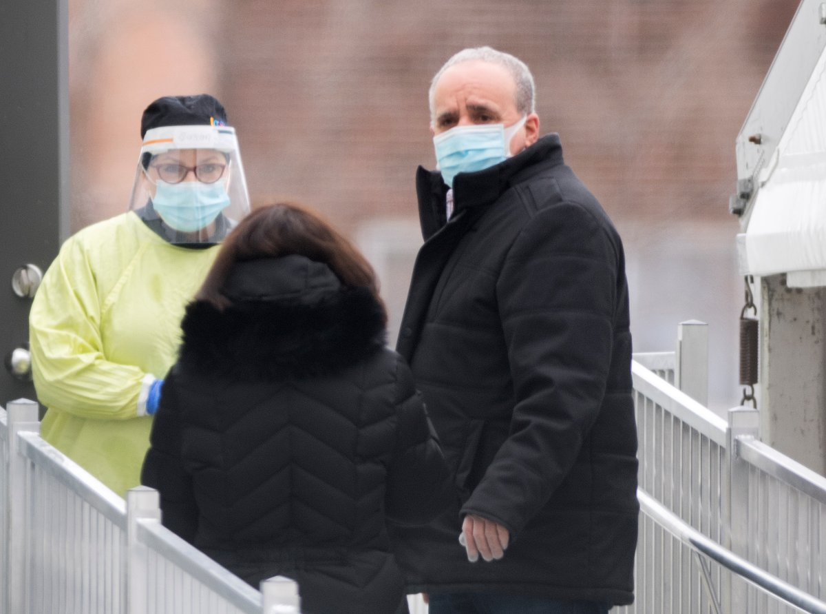 A health-care worker talks with people as they wait outside a COVID-19 testing clinic in Montreal, Sunday, January 3, 2021, as the COVID-19 pandemic continues in Canada and around the world.