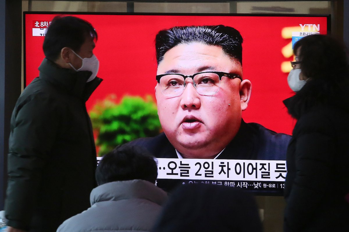 People walk by a TV screen showing North Korean leader Kim Jong Un during a ruling party congress, at the Seoul Railway Station in Seoul, South Korea, Wednesday, Jan. 6, 2021.