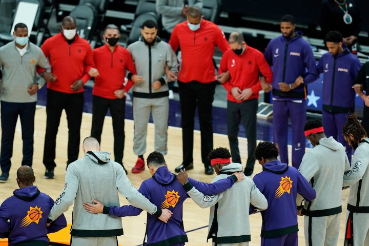 Members of the Phoenix Suns and the Toronto Raptors form a circle during the American national anthem prior to an NBA basketball game Wednesday, Jan. 6, 2021, in Phoenix.