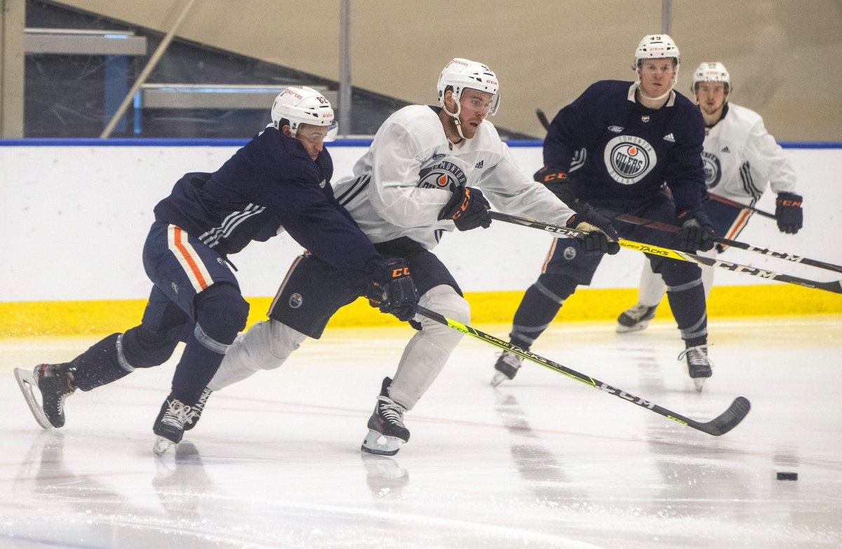 Connor McDavid (97) and Caleb Jones (82) battle for the puck during a scrimmage at the Edmonton Oilers training camp in Edmonton, Alta., on Thursday January 7, 2021. THE CANADIAN PRESS/Jason Franson.