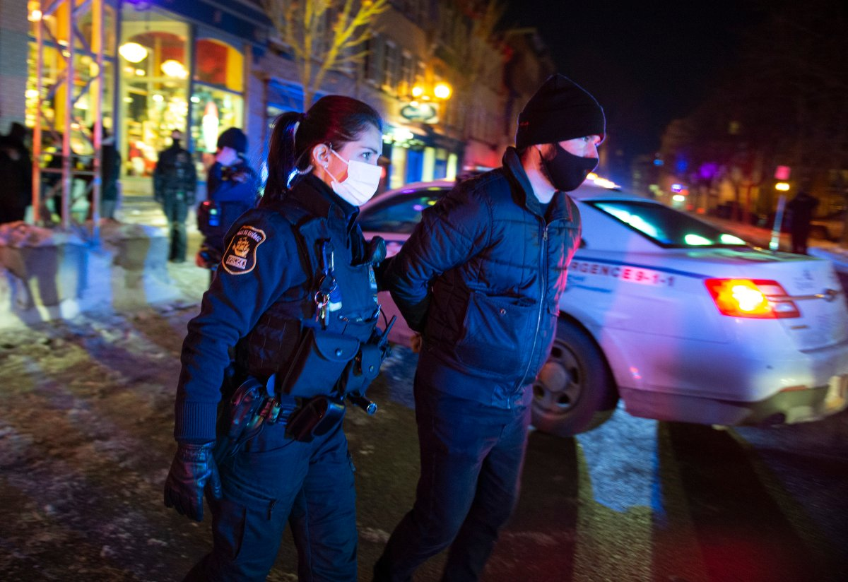 A man is arrested by police after 8 p.m. as a curfew begins in the province of Quebec to counter the spread of COVID-19 on Saturday, January 9, 2021 in Quebec City. A handful of demonstrators walked downtown to protest the curfew.