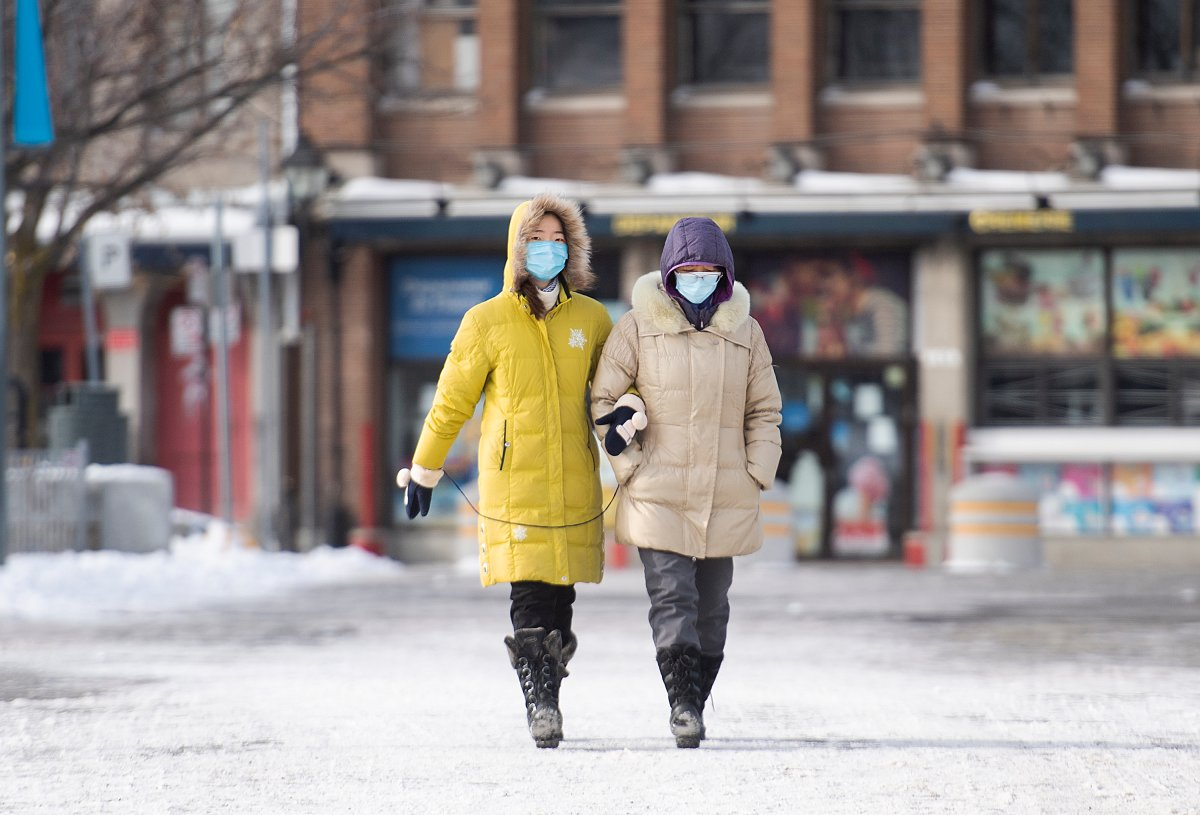 People wear face masks as they walk in the Old Port in Montreal, Sunday, January 10, 2021, as the COVID-19 pandemic continues in Canada and around the world. The Quebec government has imposed a lockdown and a curfew to help stop the spread of COVID-19. The curfew begins at 8 p.m until 5 a.m and lasting until February 8.