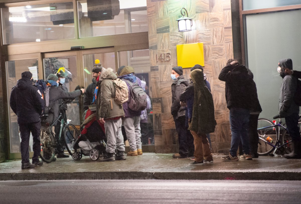 People line-up at a hotel for the homeless before the 8 p.m.   COVID-19 curfew Monday, January 11, 2021 in Montreal.