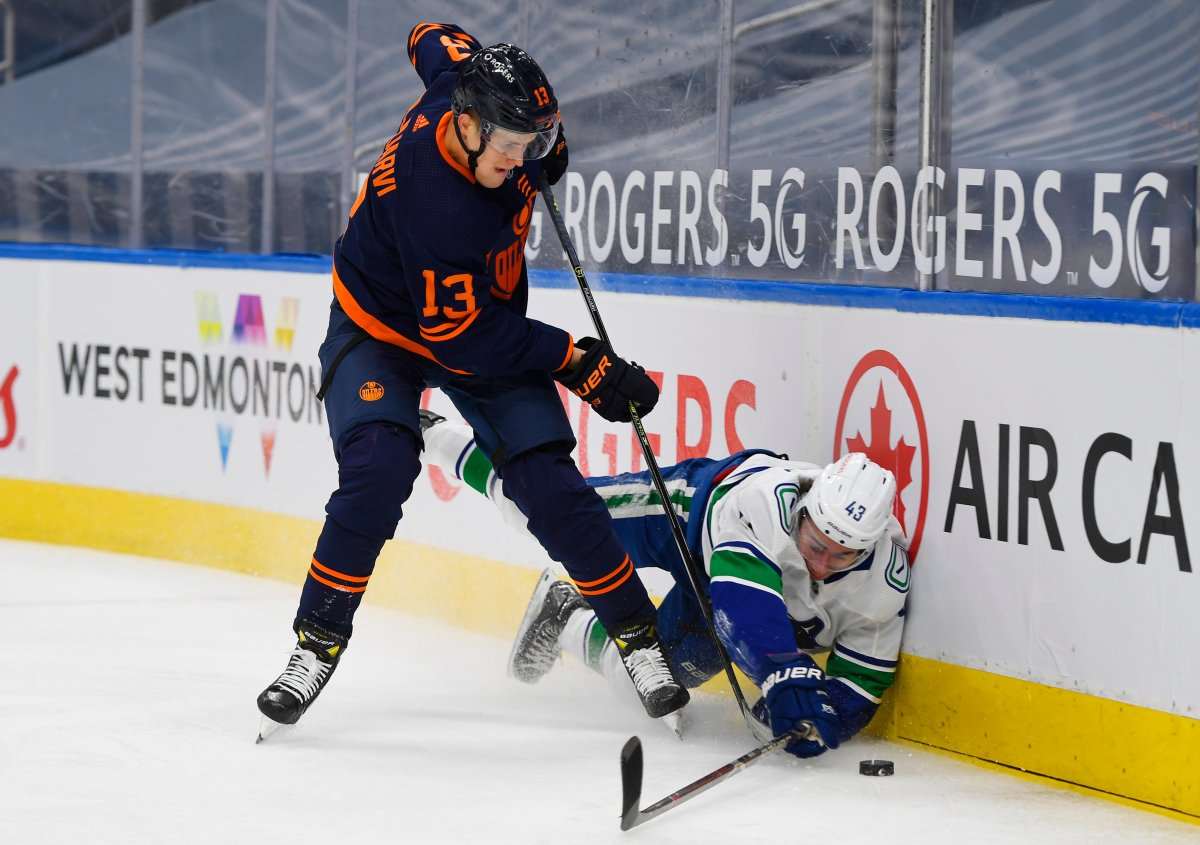 Edmonton Oilers' Jesse Puljujarvi (13) checks Vancouver Canucks' Quinn Hughes (43) during second period NHL action in Edmonton on Wednesday, January 13, 2021. THE CANADIAN PRESS/Dale MacMillan.
