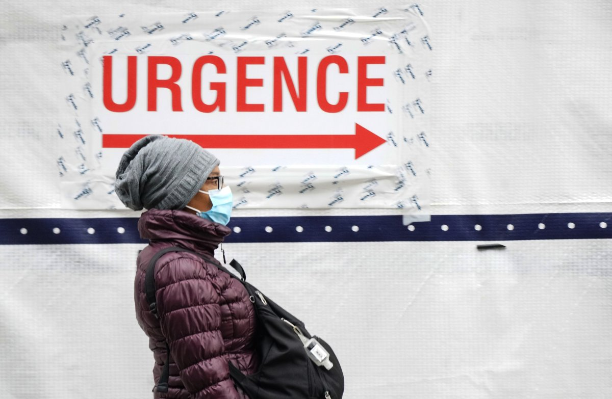 Masked woman walking in front of an emergency hospital sign in Montreal, Que., Wednesday ,January 13, 2021.