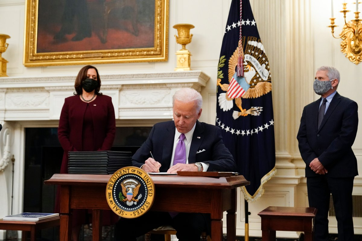 President Joe Biden signs executive orders after speaking about the coronavirus, accompanied by Vice President Kamala Harris, left, and Dr. Anthony Fauci, director of the National Institute of Allergy and Infectious Diseases, right, in the State Dinning Room of the White House, Thursday, Jan. 21, 2021, in Washington.