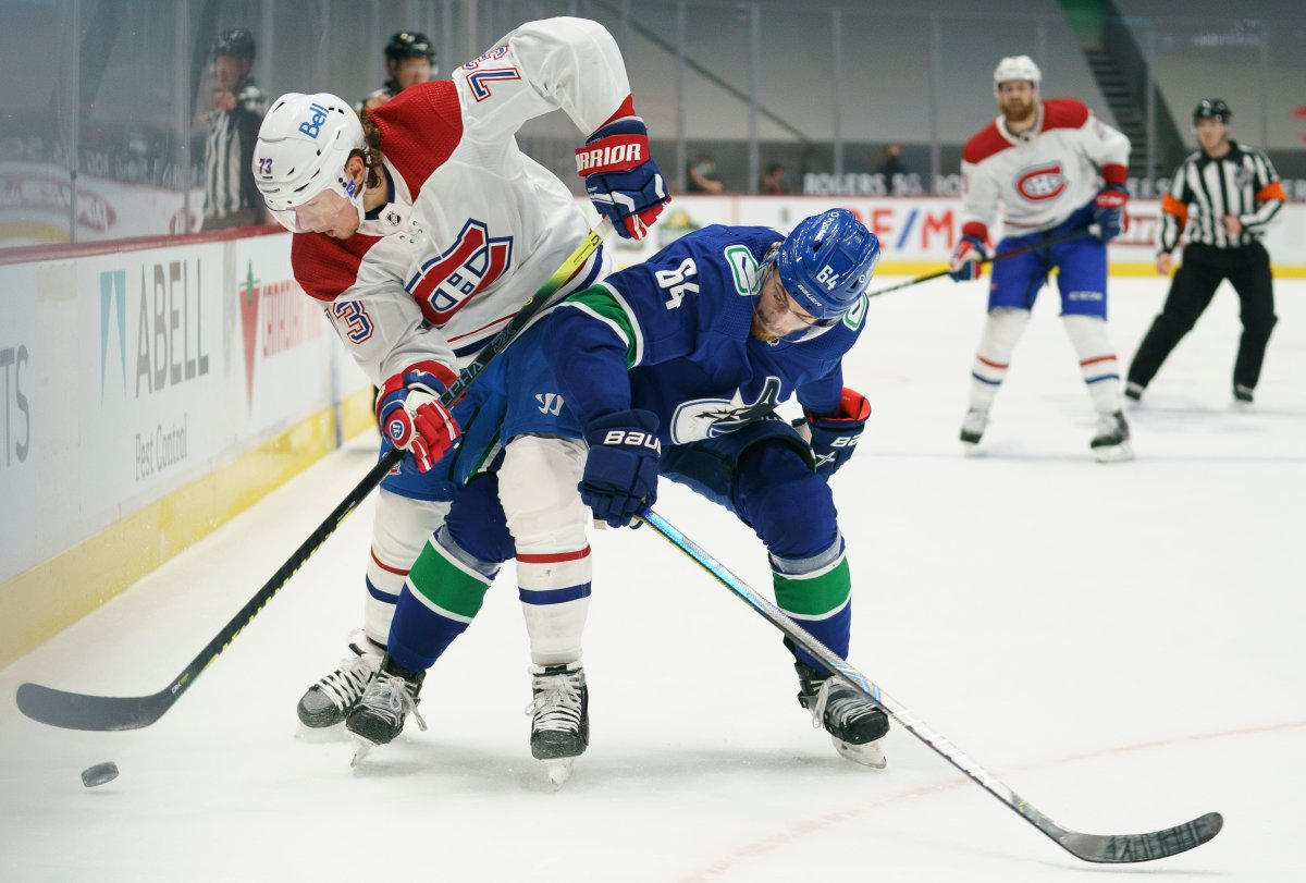 Vancouver Canucks centre Tyler Motte (64) fights for control of the puck with Montreal Canadiens right wing Tyler Toffoli (73) during first period NHL action in Vancouver on Thursday, Jan. 21, 2021.