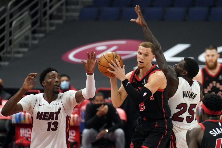Toronto Raptors guard Malachi Flynn (8) goes up for a shot between Miami Heat center Bam Adebayo (13) and guard Kendrick Nunn (25) during the first half of an NBA basketball game Friday, Jan. 22, 2021, in Tampa, Fla.