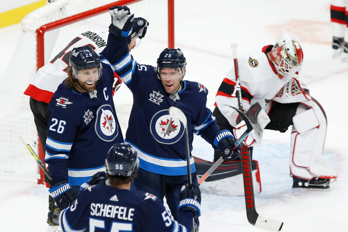 Winnipeg Jets' Mark Scheifele (55), Blake Wheeler (26) and Paul Stastny (25) celebrate Stastny's game winning goal against Ottawa Senators goaltender Marcus Hogberg (1) during third period NHL action in Winnipeg on Saturday, January 23, 2021.