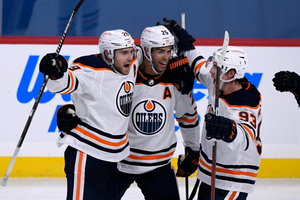 Edmonton Oilers' Leon Draisaitl (29) celebrates his game-winning goal against the Winnipeg Jets with teammates Darnell Nurse (25) and Ryan Nugent-Hopkins (93) during third period NHL action in Winnipeg on Sunday Jan. 24, 2021. THE CANADIAN PRESS/Fred Greenslade.