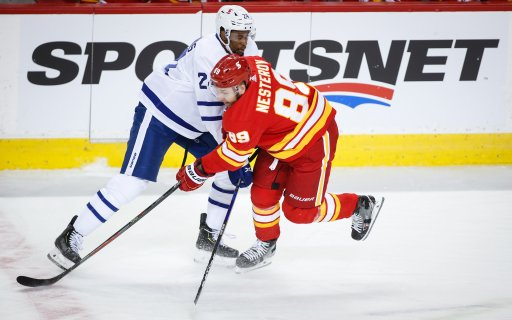 Toronto Maple Leafs' Wayne Simmonds, left, is checked by Calgary Flames' Nikita Nesterov during first period NHL hockey action in Calgary, Tuesday, Jan. 26, 2021.