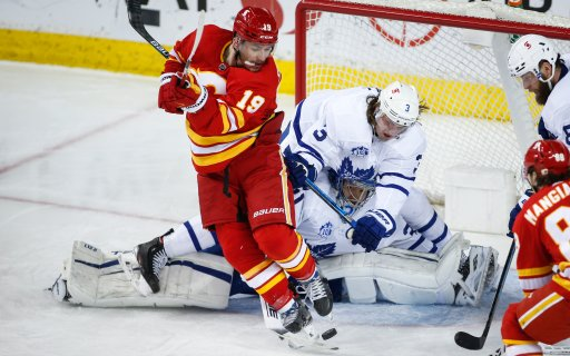 Toronto Maple Leafs' Justin Holl, right, crashes over goalie Frederik Andersen, centre, trying keep Calgary Flames' Matthew Tkachuk from the puck during second period NHL hockey action in Calgary, Tuesday, Jan. 26, 2021.