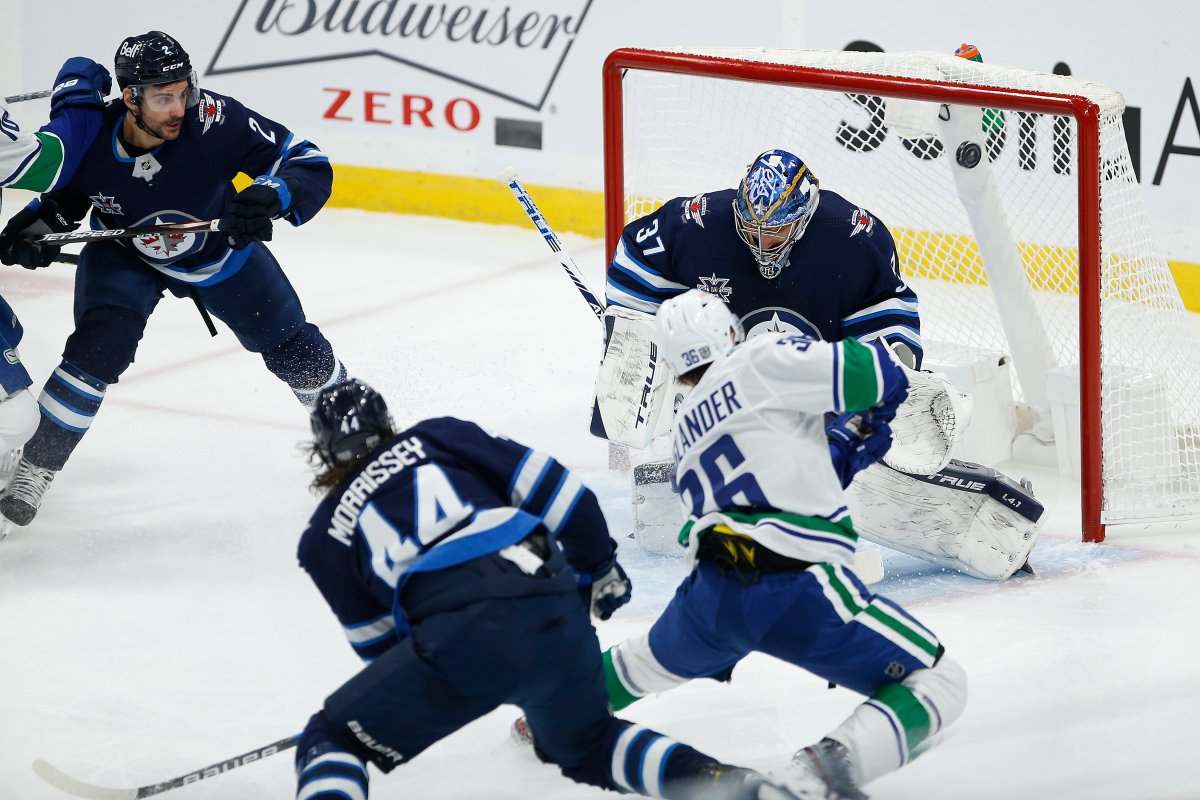 Winnipeg Jets goaltender Connor Hellebuyck (37) stops the shot from Vancouver Canucks' Nils Hoglander (36) during first period NHL action in Winnipeg on Saturday, January 30, 2021.