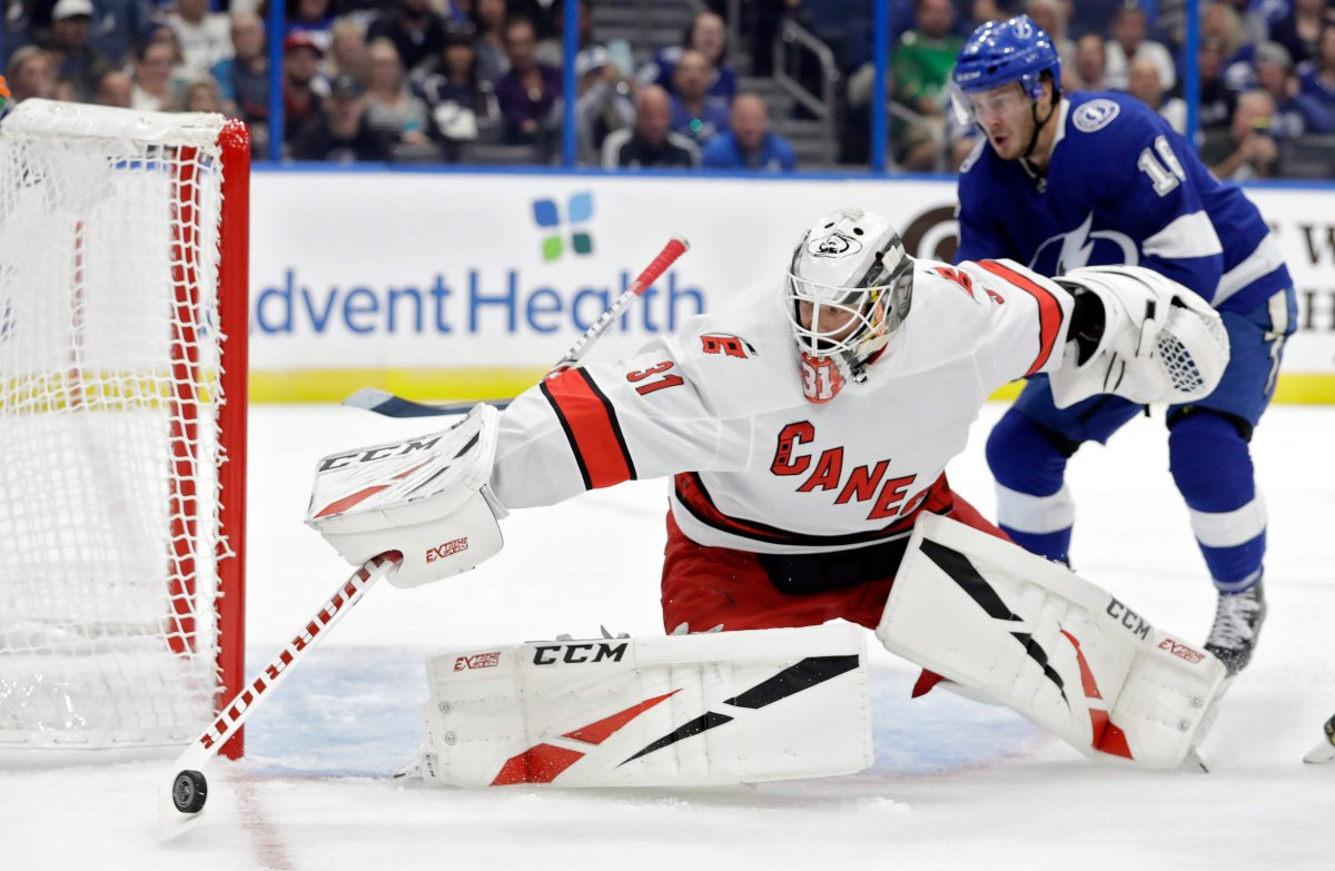 Carolina Hurricanes goaltender Anton Forsberg (31) makes a save on a shot as Tampa Bay Lightning right wing Taylor Raddysh (16) looks for a rebound during the second period of an NHL preseason hockey game Tuesday, Sept. 17, 2019, in Tampa, Fla. (AP Photo/Chris O'Meara).