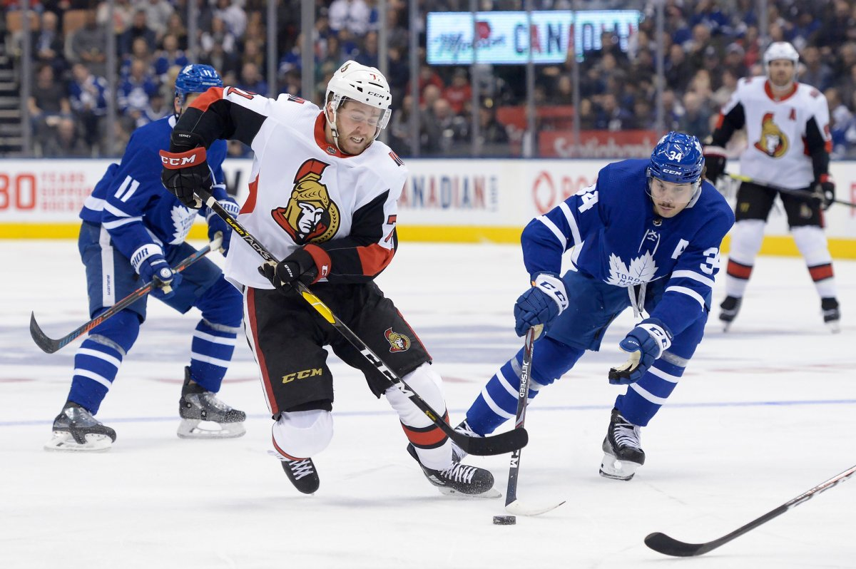 Ottawa Senators centre Chris Tierney (71) and Toronto Maple Leafs centre Auston Matthews (34) battle for the puck during first period NHL hockey action in Toronto, Saturday, Feb. 1, 2020.