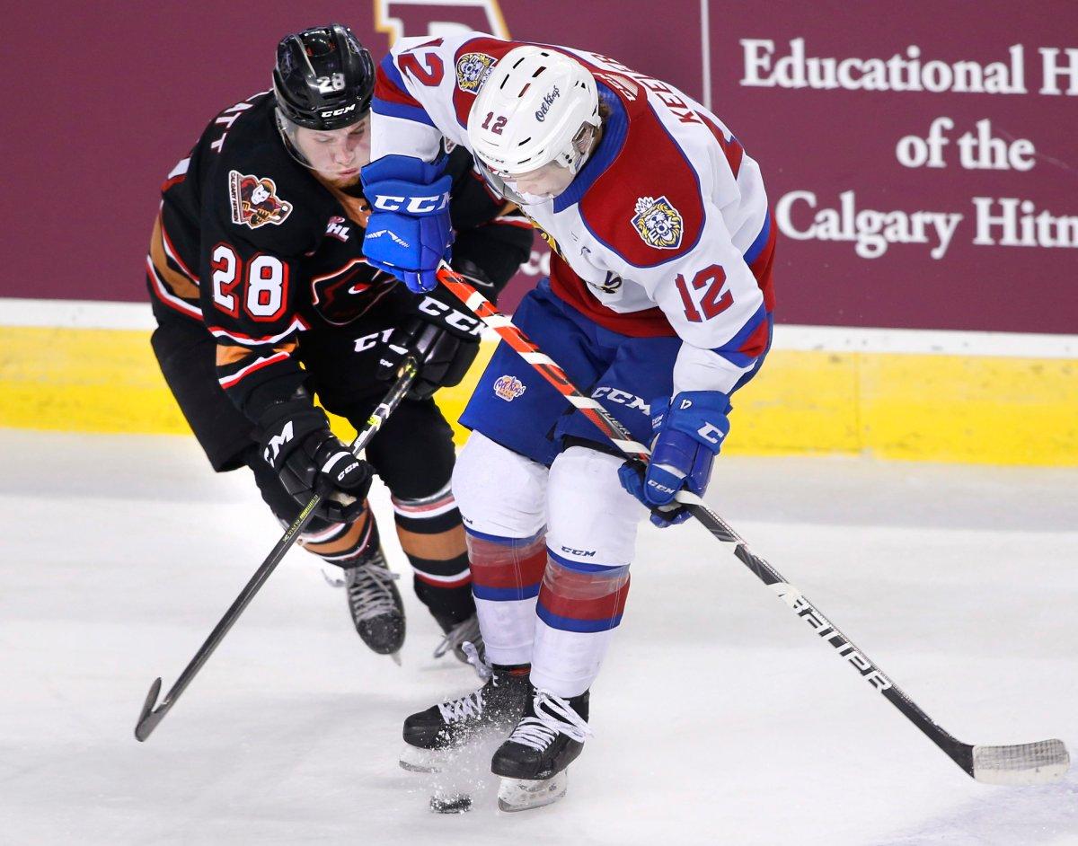 Edmonton Oil Kings player Liam Keeler, rt, battles for the puck with Calgary Hitmen player Orca Wiesblatt during WHL (Western Hockey League) hockey action in Calgary, Alta., on Friday, Dec. 6, 2019.