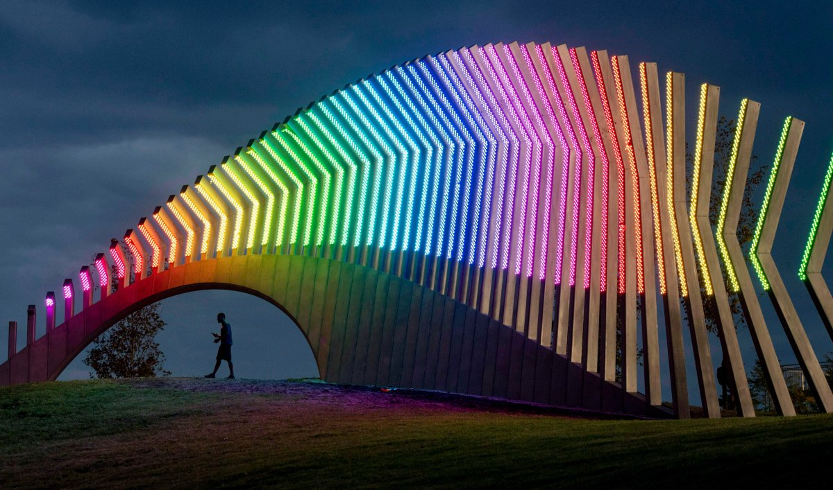 A man walks under Moving Surfaces, a giant steel and light sculpture at Ottawa's Lansdowne Park, as it is lit up in the colours of the rainbow, during Pride Week on Saturday, Aug. 25, 2018.
