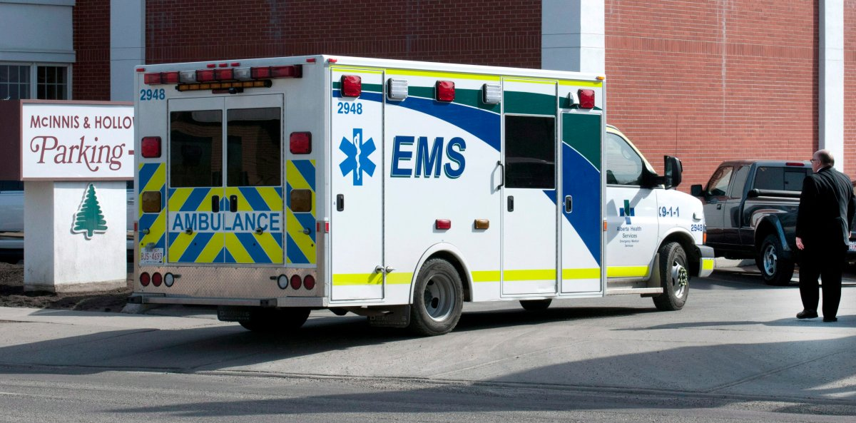 An ambulance arrives after a mourner collapsed at the funeral for Jordan Segura, one of the victims of an April 15 mass stabbing attack, in Calgary on Monday, April 21, 2014.