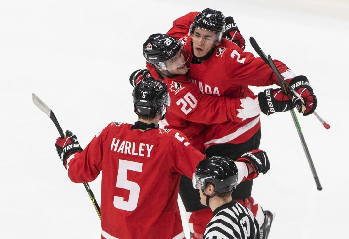 Canada defenseman Braden Schneider (2) celebrates his goal with teammates Thomas Harley (5) and Dawson Mercer (20) against Russia during second period IIHF World Junior Hockey Championship action in Edmonton on Monday, January 4, 2021.