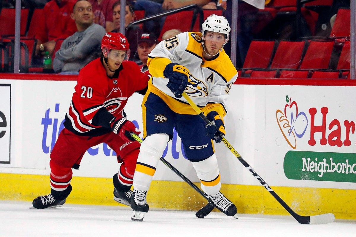 Nashville Predators' Matt Duchene (95) moves the puck away from Carolina Hurricanes' Sebastian Aho (20) during the first period of an NHL preseason hockey game, in Raleigh, N.C, Friday, Sept. 27, 2019.