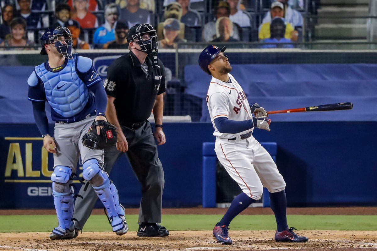 Houston Astros center fielder George Springer (R) hits a two-run home run as umpire Chris Conroy (C) and Tampa Bay Rays catcher Mike Zunino (L) look on in the fifth inning of the American League Championship Series playoff game four between the Tampa Bay Rays and the Houston Astros at Petco Park in San Diego, California, 14 October 2020.