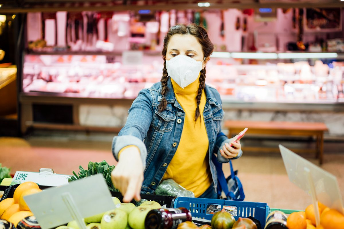 Young woman with a mask grocery shopping.