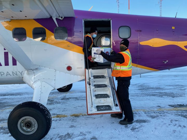 Workers unload vaccines at the La Ronge airport.