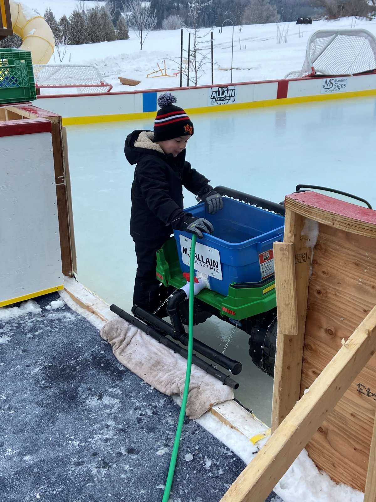 Five-year-old Nicholas Allain is seen getting ready to clear the ice in his min-Zamboni.