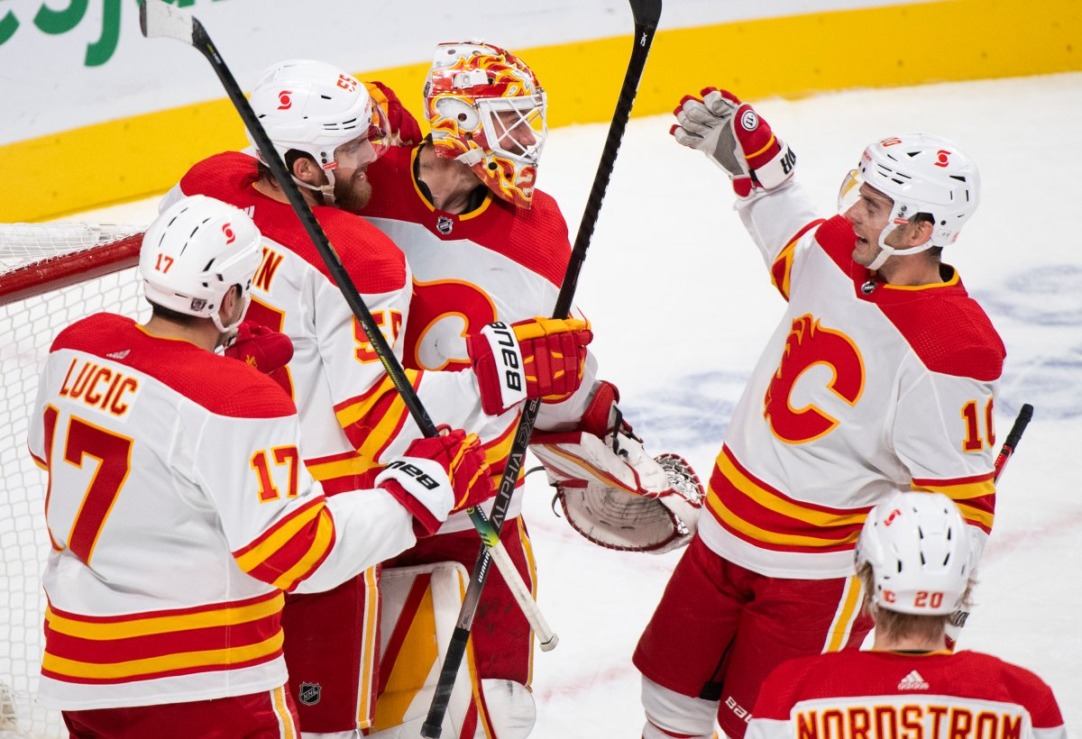 Calgary Flames goaltender Jacob Markstrom celebrates with teammates after defeating the Montreal Canadiens in an NHL hockey game in Montreal, Saturday, January 30, 2021.THE CANADIAN PRESS/Graham Hughes.