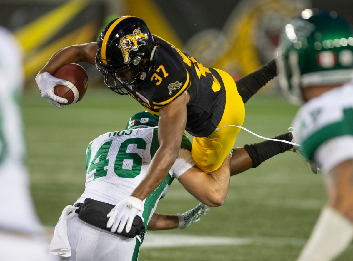Hamilton Tiger-Cats Frankie Williams goes high over the tackle of Saskatchewan Roughriders Jorgen Hus during second half CFL football game action in Hamilton, Ont. on Thursday, June 13, 2019. THE CANADIAN PRESS/Peter Power.