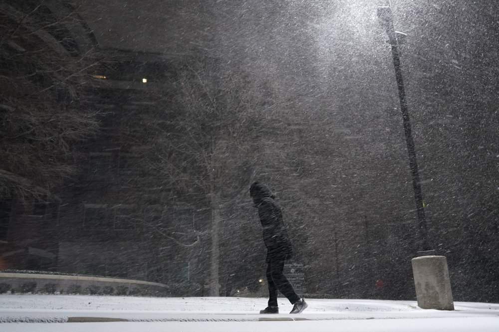A woman walks through falling snow in San Antonio, Sunday, Feb. 14, 2021. Snow and ice blanketed large swaths of the U.S. on Sunday, prompting canceled flights, making driving perilous and reaching into areas as far south as Texas' Gulf Coast, where snow and sleet were expected overnight.