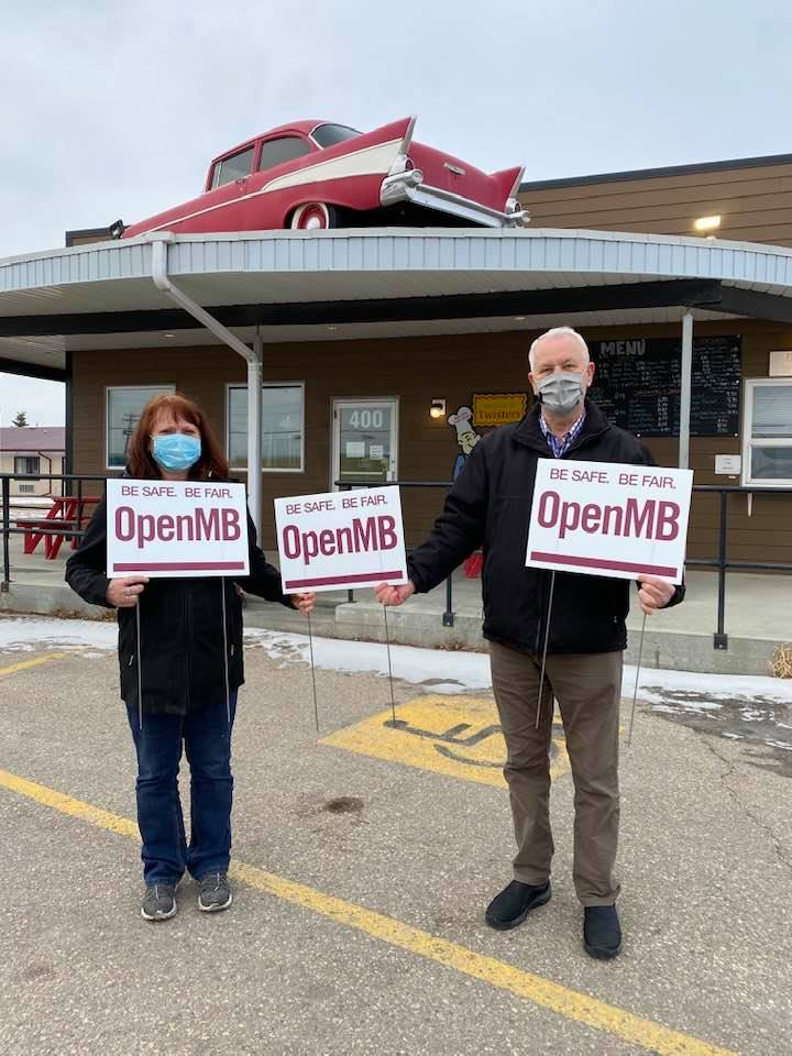 Winkler Mayor Martin Harder (right) stands with a business owner in his town.