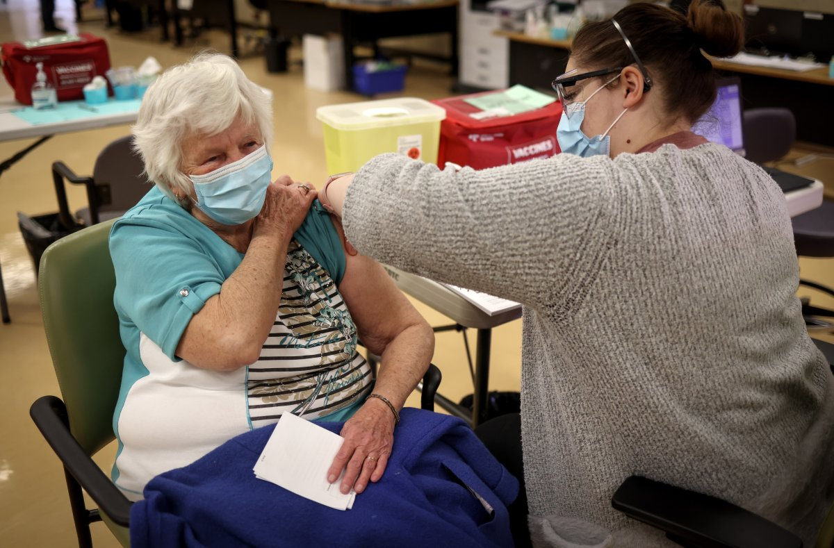 Mary House, 80, receives the COVID-19 vaccine from Alyssa Zaderey in Calgary on Wednesday, Feb. 24, 2021.