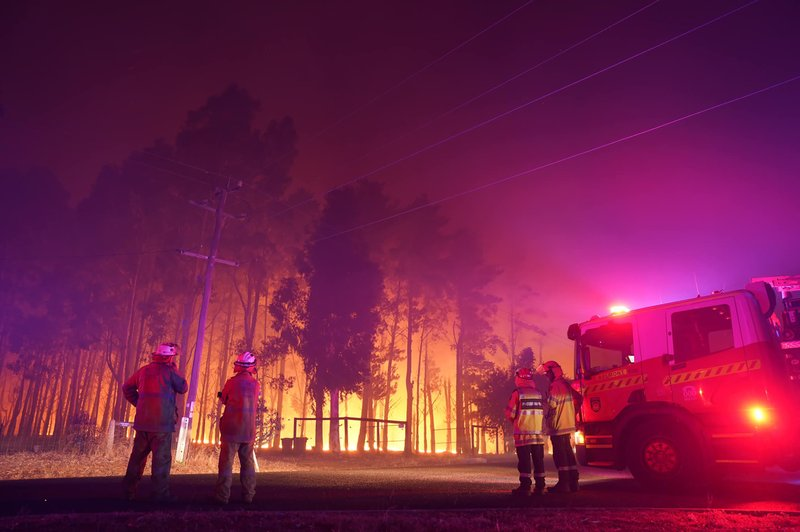 Firefighters attend a fire at Wooroloo, near Perth, Australia, Monday, Feb. 1, 2021. An out-of-control wildfire burning northeast of the Australian west coast city of Perth has destroyed an estimated 30 homes and was threatening more Tuesday, with many locals across the region told it is too late to leave.