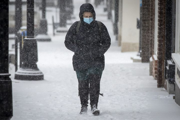 A person wears a mask during a snow squall in Kingston, Ontario on Tuesday, January 26, 2021.