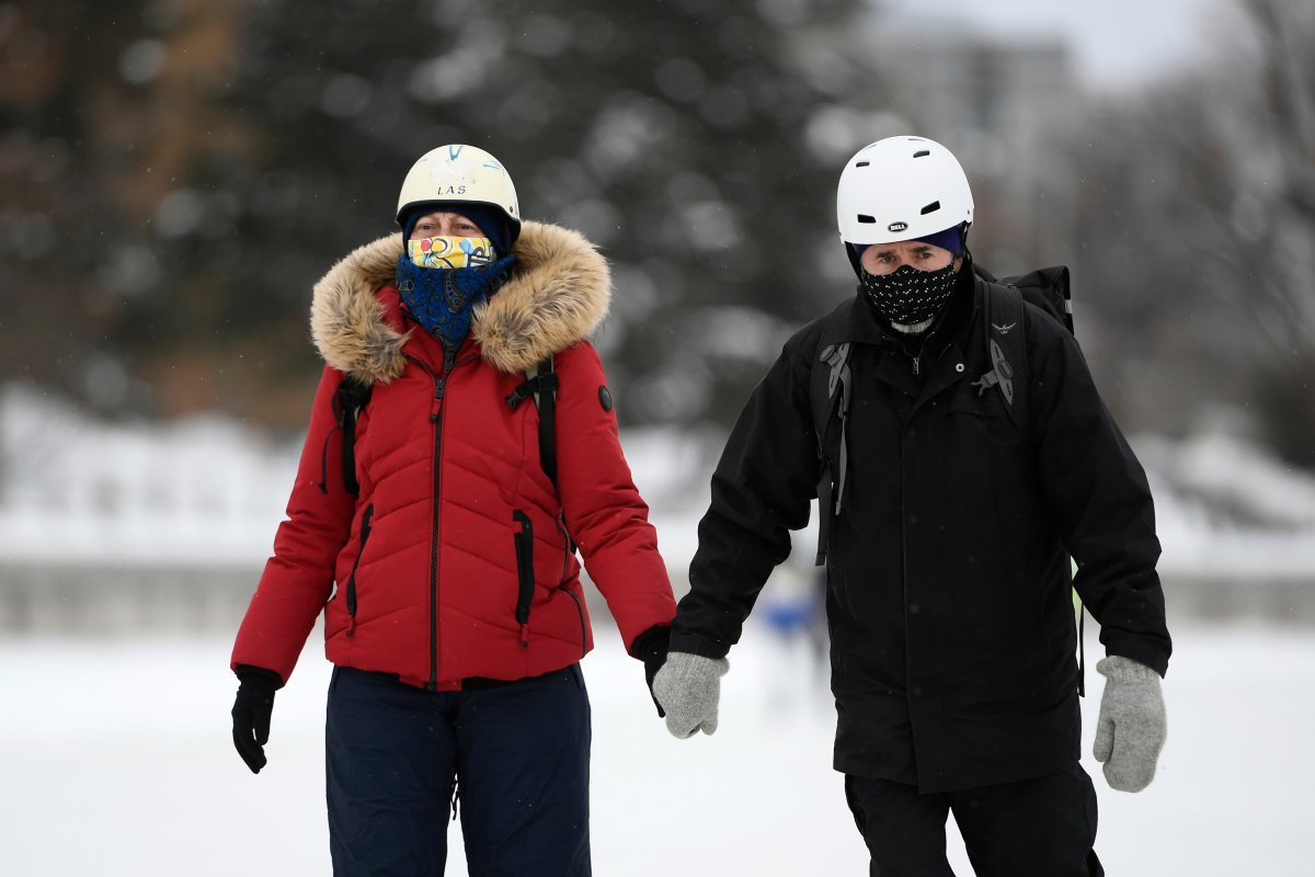 People wear masks as they make their way along the Rideau Canal Skateway on its opening day in Ottawa, on Thursday, Jan. 28, 2021, in the midst of the COVID-19 pandemic. The Rideau Canal is a UNESCO World Heritage Site.