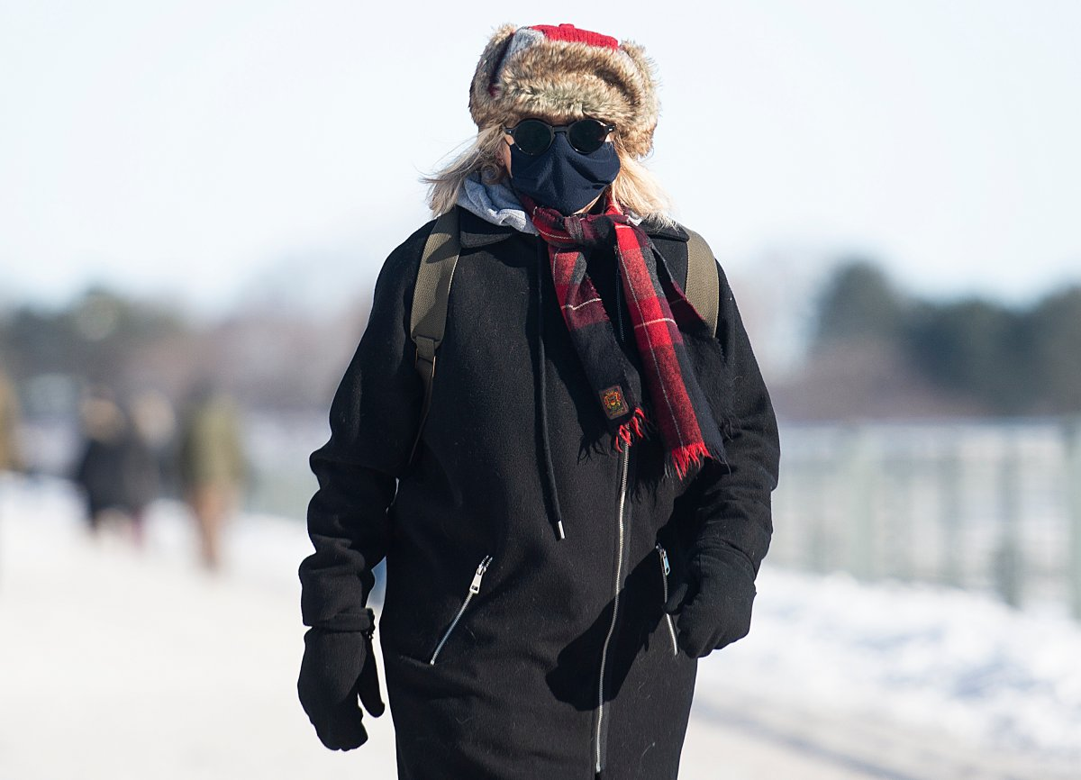 A woman wears a face mask as she braves the cold in Montreal, Sunday, Jan. 31, 2021, as the COVID-19 pandemic continues in Canada and around the world.