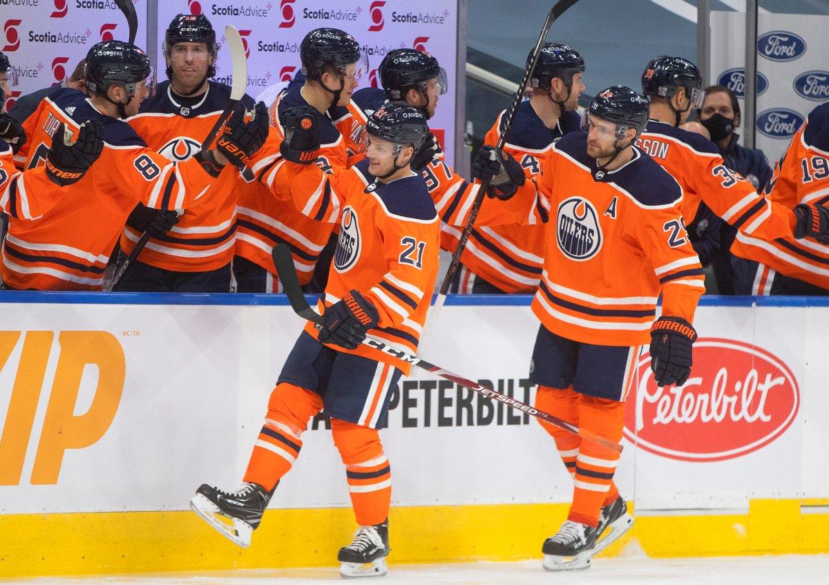 Edmonton Oilers' Dominik Kahun (21) and Leon Draisaitl (29) celebrate Kahun's goal against the Ottawa Senators with teammates on the bench during first period NHL action in Edmonton on Sunday, January 31, 2021. THE CANADIAN PRESS/Jason Franson.