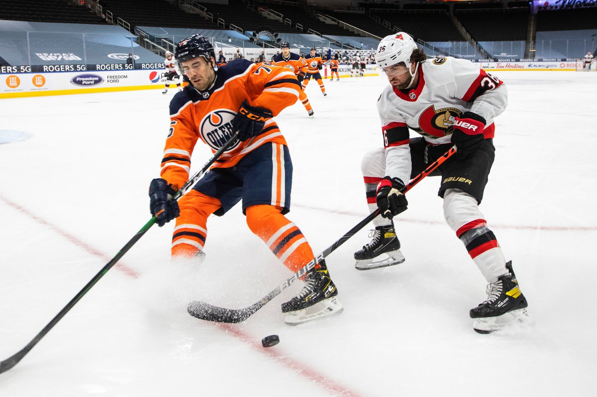 Edmonton Oilers' Evan Bouchard (75) and Ottawa Senators' Colin White (36) battle for the puck during first period NHL action in Edmonton on Tuesday, February 2, 2021.