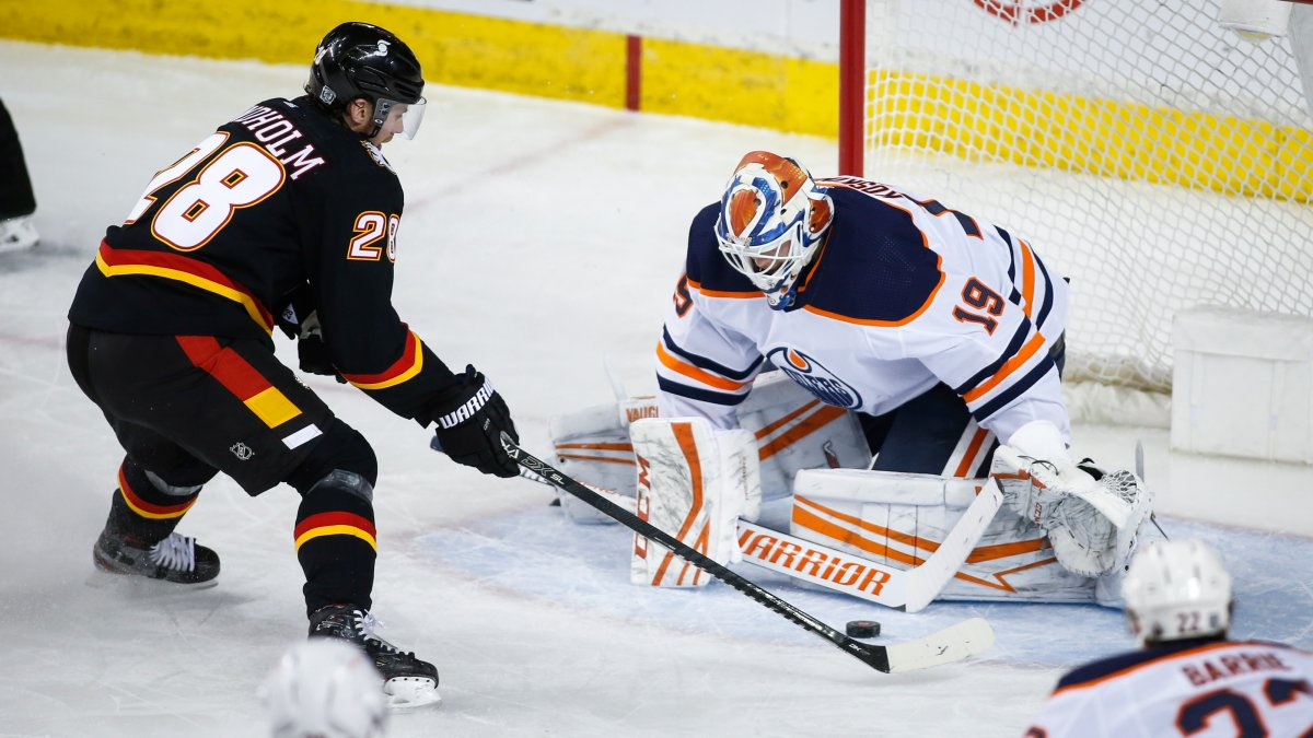 Edmonton Oilers goalie Mikko Koskinen, right, stops Calgary Flames' Elias Lindholm during second period NHL hockey action in Calgary, Saturday, Feb. 6, 2021.THE CANADIAN PRESS/Jeff McIntosh.