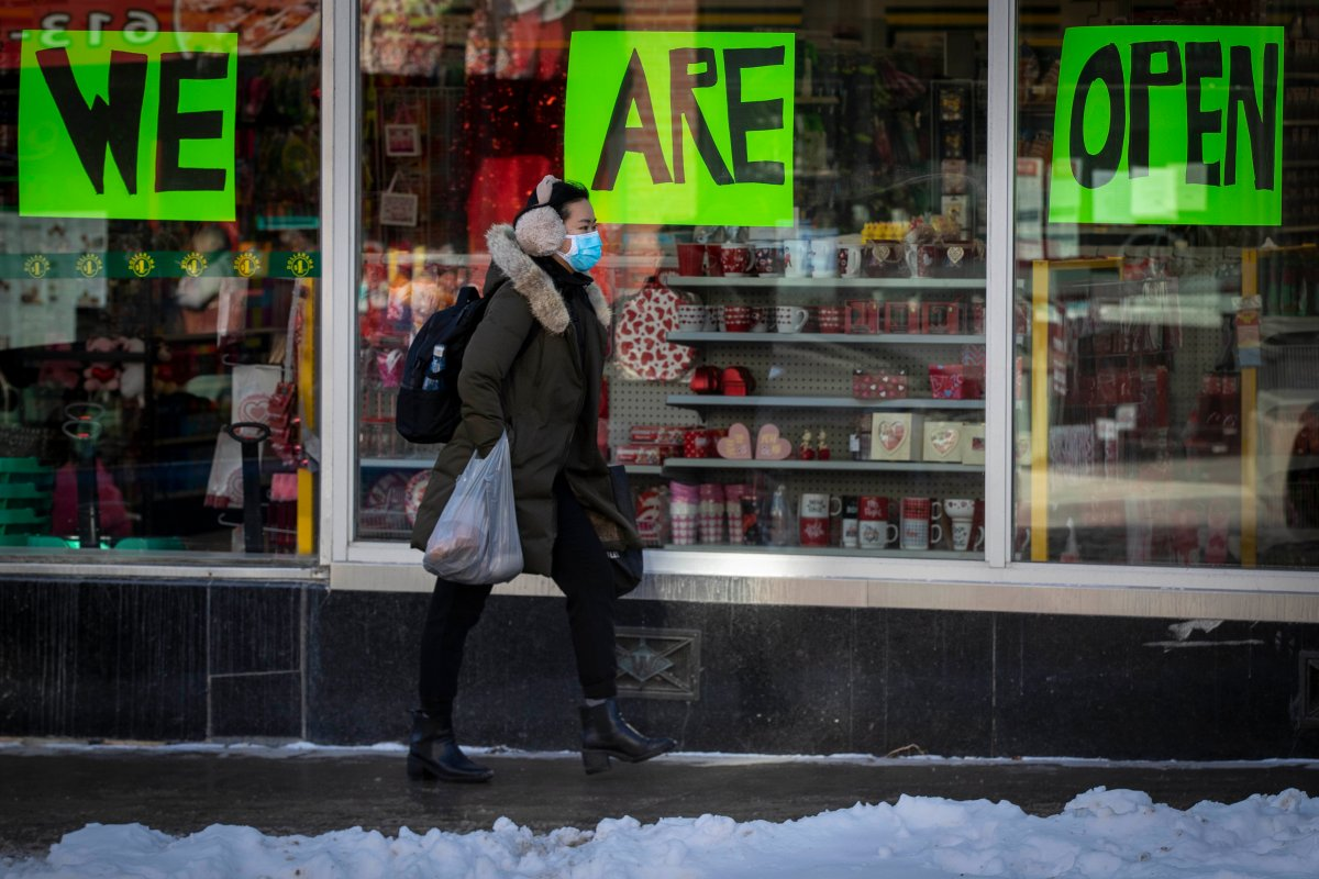 A person wears a mask to protect them from the COVID-19 virus while walking by an open store in Kingston, Ontario, on Wednesday Feb. 10, 2021. Kingston, Frontenac and Lennox & Addington (KFL&A) Public Health unit has moved into the green zone.