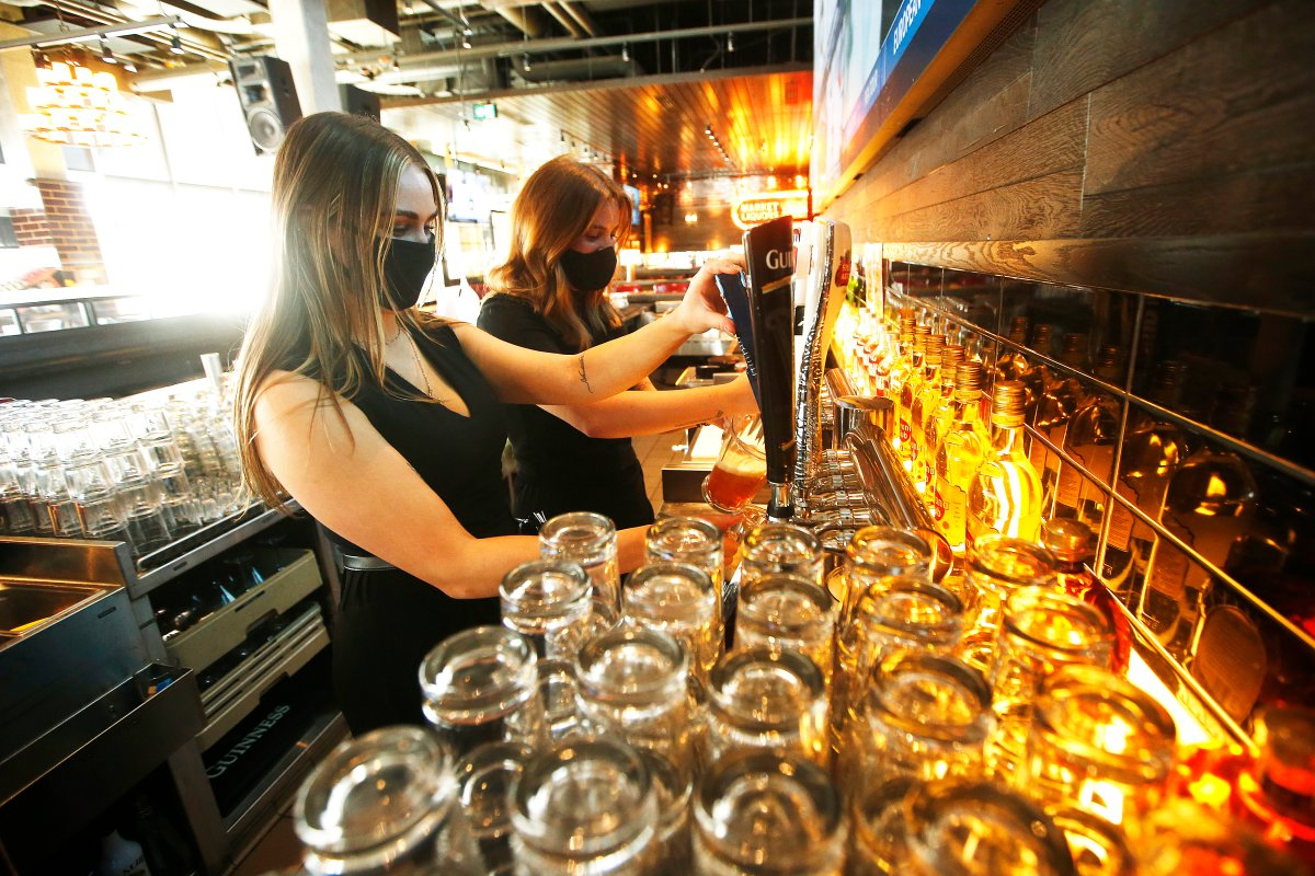 Browns Socialhouse bar manager, Jaz Hrem, left, and server Claire McCarvill set up the bar in preparation of re-opening as some COVID-19 restrictions are lifted in Winnipeg, Friday, February 12, 2021.