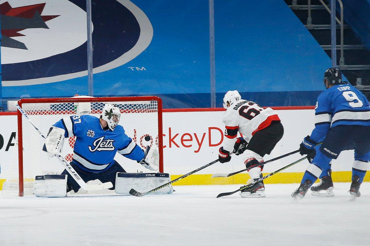 Ottawa Senators' Evgenii Dadonov (63) scores against Winnipeg Jets goaltender Connor Hellebuyck (37) during second period NHL action in Winnipeg on Saturday, February 13, 2021.