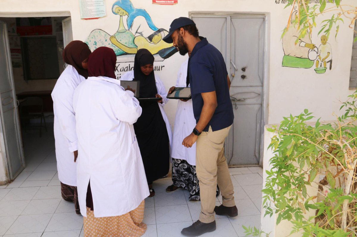 Canadian Khalid Hashi, right, shows informative videos about COVID-19 in his app OGOW EMR in Garowe, Puntland, Somalia, to frontline nurses and healthcare workers in an undated handout photo. Before Hashi created the app, which contains informative videos in Somali and Arabic about the novel coronavirus, Somalia only had public health messages about COVID-19 in English.