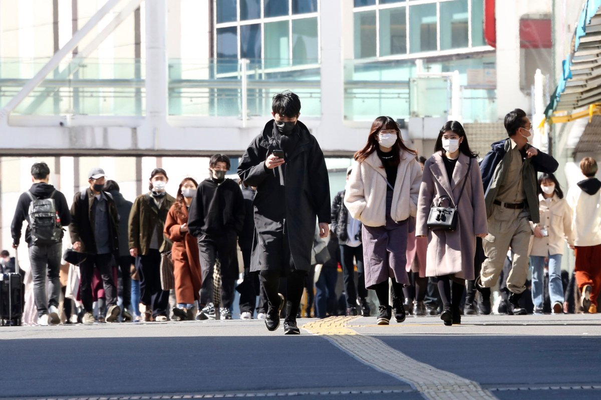 People wearing face masks to protect against the spread of the coronavirus walk on a street in Tokyo, Wednesday, Feb. 17, 2021.
